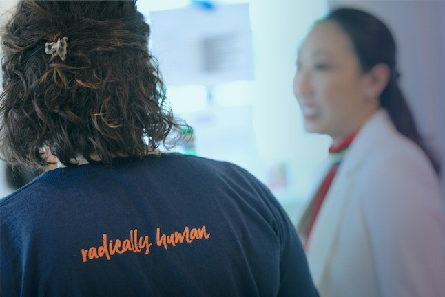 "Candid photo of two Promise54 staff members talking. One's back is to the camera, wearing a blue shirt that reads ""radically human"" in orange letters. The other is out of focus, wearing a white blazer."